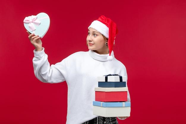 Vista frontale giovane femmina con regali di capodanno su sfondo rosso