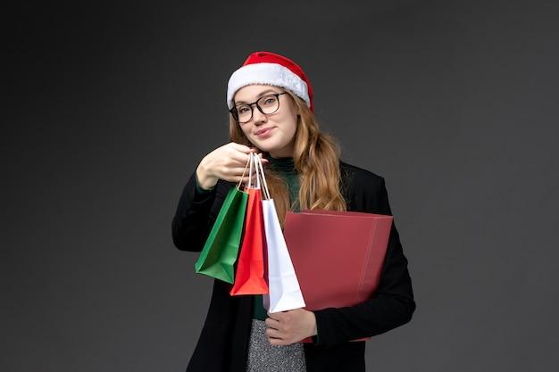 暗い壁のギフト新年クリスマスのパッケージと正面図若い女性