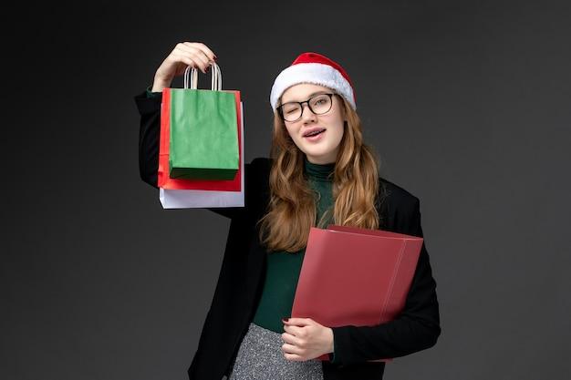 暗い床のギフト新年クリスマスのパッケージと正面図若い女性