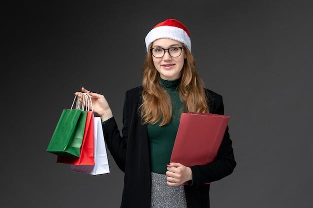 暗い壁のギフト新年クリスマスプレゼントのパッケージと正面図若い女性