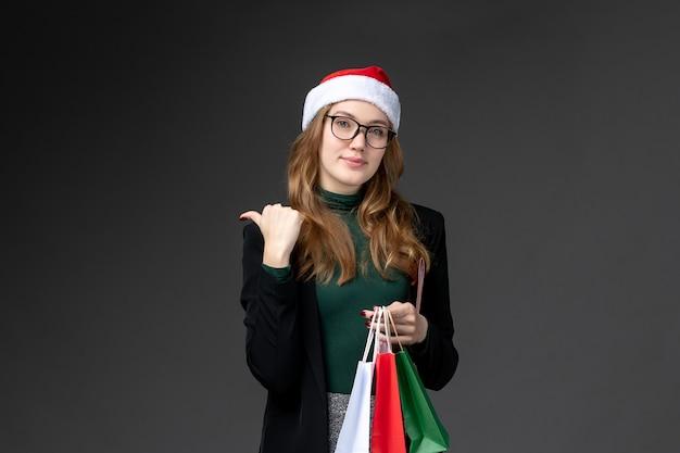 暗い壁のホリデーギフトのパッケージで新年を提示する正面図若い女性
