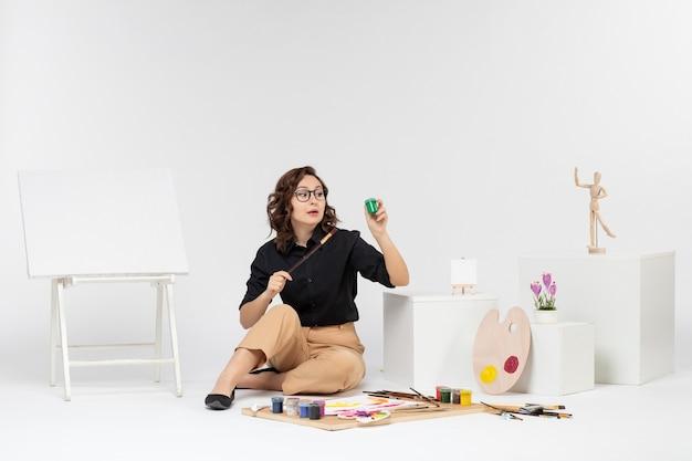 페인트와 흰색 배경에 페인트 붓을 들고 이젤 전면보기 젊은 여성