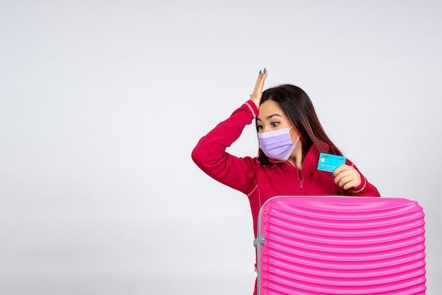 白い壁に銀行カードを保持しているマスクのピンクのバッグを持つ若い女性の正面図ウイルス女性休暇covid-カラー旅行パンデミック