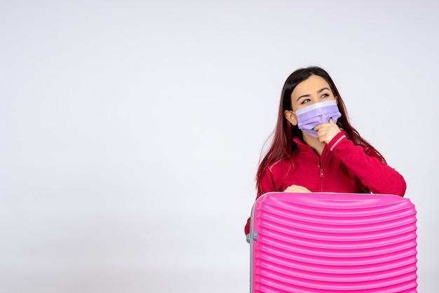 흰 벽 바이러스 휴가 유행성 여행 여자 covid- 에지도를 들고 마스크에 분홍색 가방 전면보기 젊은 여성