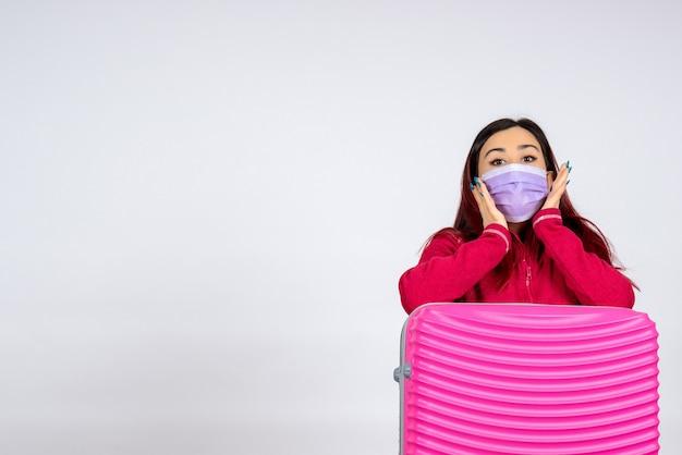 Вид спереди молодая женщина с розовой сумкой в маске держит карту на белой стене женщина цветной вирус отпуск пандемическая поездка covid-