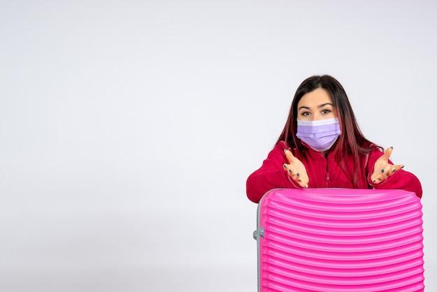 흰 벽 바이러스 여자 휴가 covid- 컬러 여행 전염병에 마스크에 핑크 가방 전면보기 젊은 여성