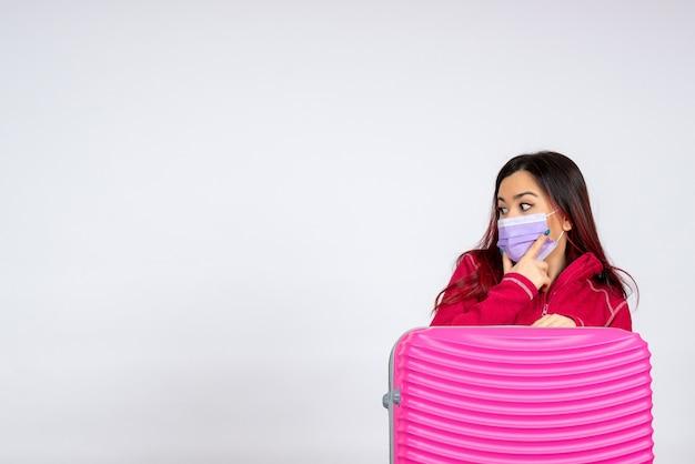 흰 벽 유행성 바이러스 여자 휴가 covid- 컬러 여행에 마스크에 분홍색 가방 전면보기 젊은 여성