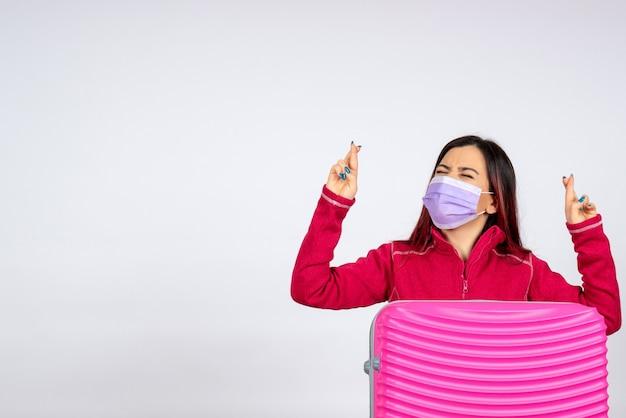 흰 벽 휴가 유행성 바이러스 covid- 색상 여행 여자에 마스크에 분홍색 가방 전면보기 젊은 여성