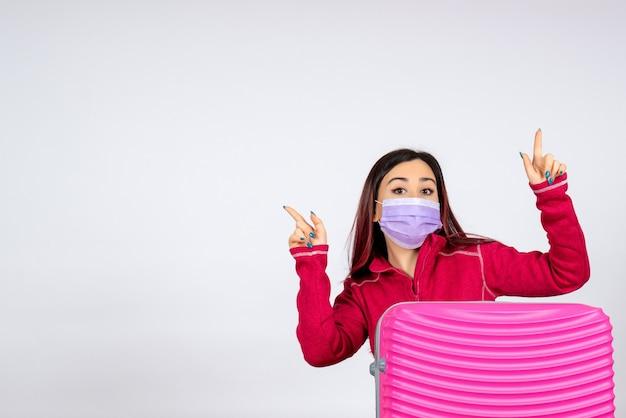 흰 벽 휴가 유행성 바이러스 여자 covid- 색상에 마스크에 분홍색 가방 전면보기 젊은 여성