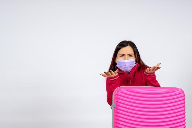 흰 벽 바이러스 휴가 covid 색상 유행에 마스크에 핑크 가방 전면보기 젊은 여성