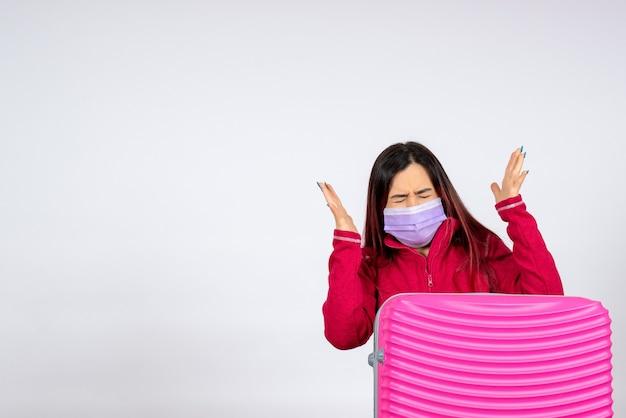 흰 벽 바이러스 휴가 covid 유행성 여행 여자에 마스크에 분홍색 가방 전면보기 젊은 여성