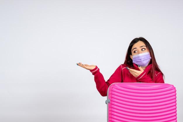 흰 벽에 마스크에 분홍색 가방을 가진 전면보기 젊은 여성 바이러스 여자 covid 색상 유행병