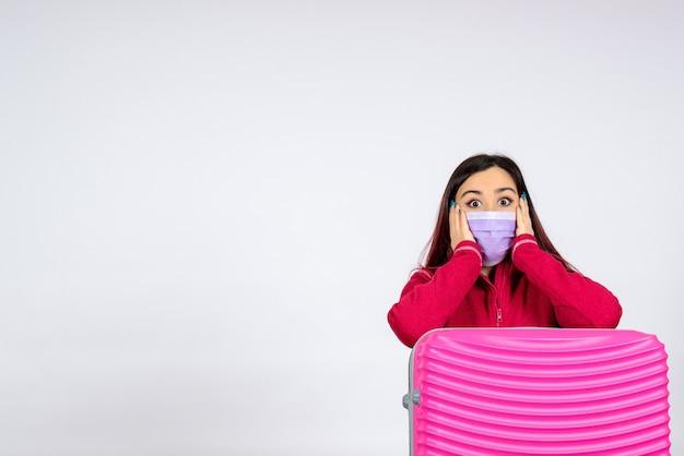 Вид спереди молодая женщина с розовой сумкой в маске, удивленная на белой стене, отпуск пандемического вируса женщина covid- color trip