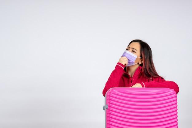Вид спереди молодая женщина с розовой сумкой в маске, думающая о вирусе отпуска на белой стене, пандемия цветного путешествия