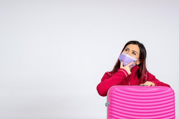 白い壁のウイルス休暇covidカラーパンデミック旅行の女性を考えて滅菌マスクでピンクのバッグを持つ若い女性の正面図