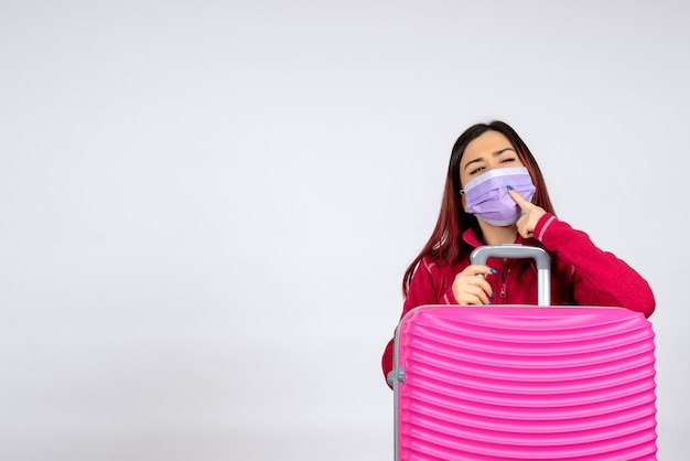 Вид спереди молодая женщина с розовым мешком в стерильной маске, думающая на белой стене, поездка, цвет, отпуск, пандемия вируса covid - женщина