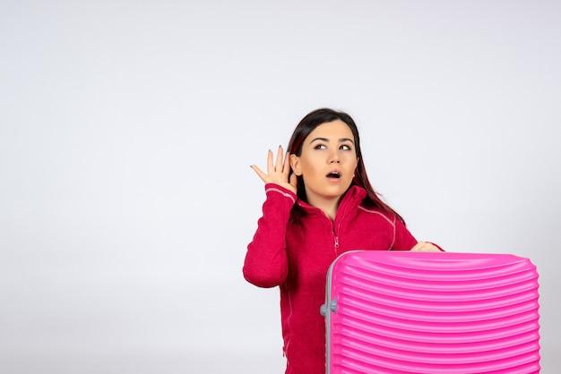 Giovane femmina di vista frontale con il sacchetto rosa che ascolta il volo di viaggio di viaggio di viaggio di colore della donna di vacanza di emozione della parete bianca
