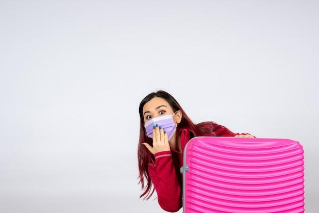Vista frontale giovane femmina con borsa rosa in maschera azienda mappa sul muro bianco virus colore vacanza pandemia viaggio covid-
