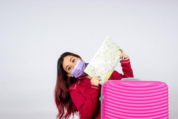 Vista frontale giovane femmina con borsa rosa in maschera azienda mappa sul muro bianco virus colore vacanza viaggio pandemico donna covid-