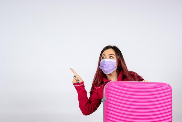 Vista frontale giovane femmina con borsa rosa in maschera azienda mappa sul muro bianco virus colore vacanza pandemia donna covid-