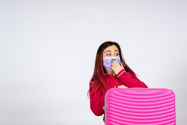 Vista frontale giovane femmina con borsa rosa in maschera sul muro bianco pandemia virus donna vacanza covid- viaggio di colore