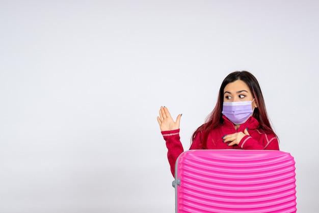 Vista frontale giovane femmina con borsa rosa in maschera sul muro bianco donna pandemia viaggio covid-virus colore