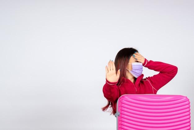 Vista frontale giovane femmina con borsa rosa in maschera sulla parete bianca vacanza pandemia covid- colore viaggio donna