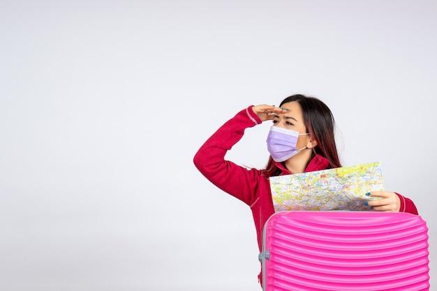 Vista frontale giovane femmina con borsa rosa in maschera sulla parete bianca vacanza pandemia virus covid- colore viaggio donna