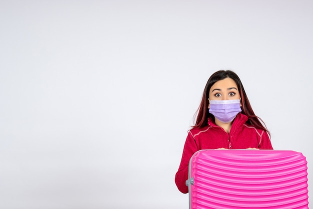 Vista frontale giovane femmina con borsa rosa in maschera sul muro bianco vacanza virus pandemico donna covid- viaggio di colore