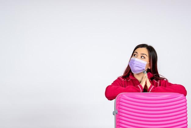 Giovane femmina di vista frontale con il sacchetto rosa nella maschera sul viaggio covid della donna del virus della pandemia di vacanza della parete bianca