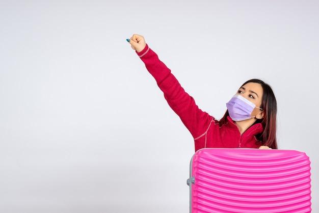 Vista frontale giovane femmina con borsa rosa in maschera sulla parete bianca vacanza virus covid colore viaggio pandemico donna
