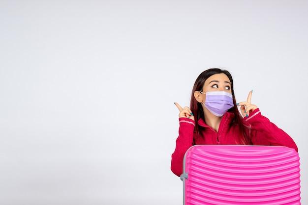 Giovane femmina di vista frontale con il sacchetto rosa nella maschera sul viaggio di pandemia di colore di covid di vacanza del virus della parete bianca