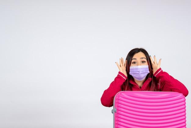 Giovane femmina di vista frontale con il sacchetto rosa nella maschera sulla donna di viaggio di colore covid di vacanza del virus della parete bianca