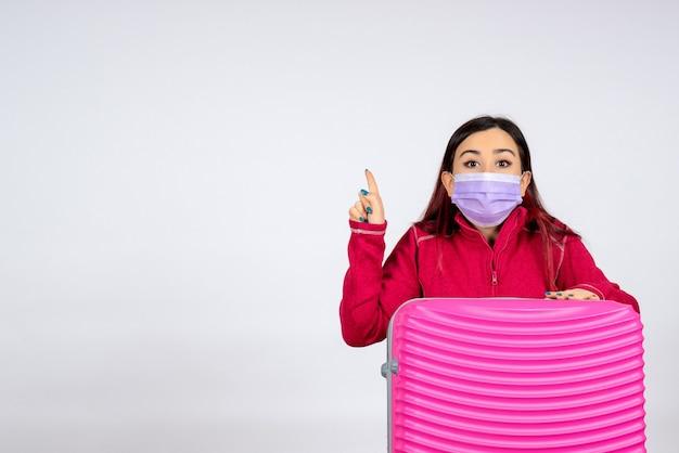 Vista frontale giovane femmina con borsa rosa in maschera sulla parete bianca virus donna covid- viaggio di colore pandemia