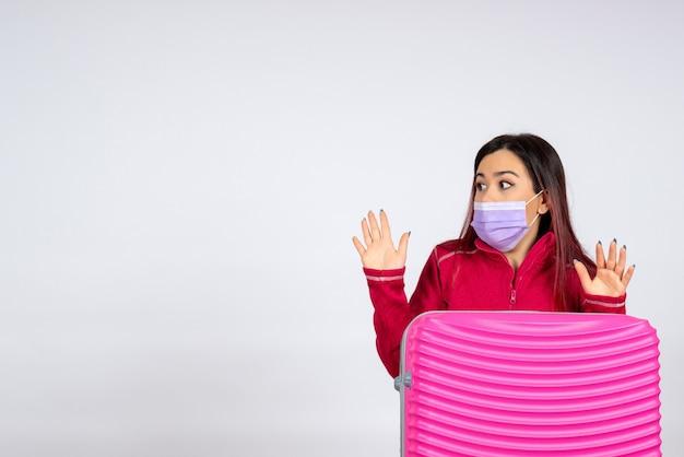 Giovane femmina di vista frontale con il sacchetto rosa nella maschera sul viaggio di pandemia di colore di vacanza della donna del virus della parete bianca