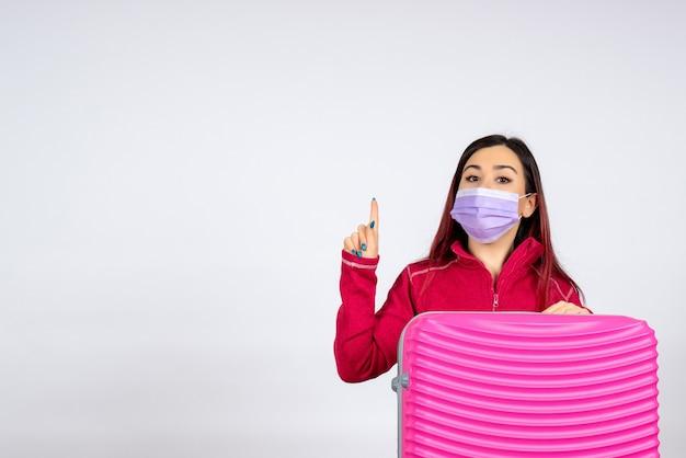 Vista frontale giovane femmina con borsa rosa in maschera sul muro bianco virus donna vacanza covid viaggio pandemico di colore