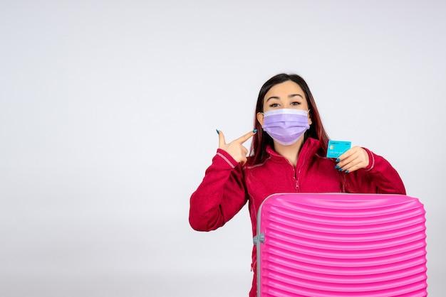 Vista frontale giovane femmina con borsa rosa in maschera sulla parete bianca virus donna vacanza covid pandemia di colore