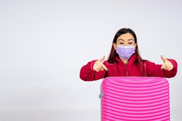 Giovane femmina di vista frontale con il sacchetto rosa nella maschera sulla pandemia di viaggio di colore di covid di vacanza della donna del virus della parete bianca