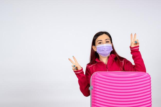 Vista frontale giovane femmina con borsa rosa in maschera sul muro bianco virus donna vacanza covid viaggio di colore