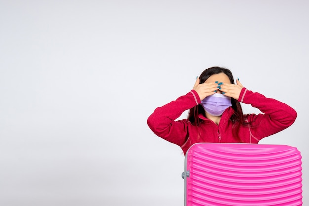 Giovane femmina di vista frontale con il sacchetto rosa nella maschera sul viaggio pandemico covid di vacanza della donna del virus della parete bianca