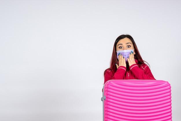 Vista frontale giovane femmina con borsa rosa in maschera sul muro bianco donna virus del colore vacanza pandemia covid-