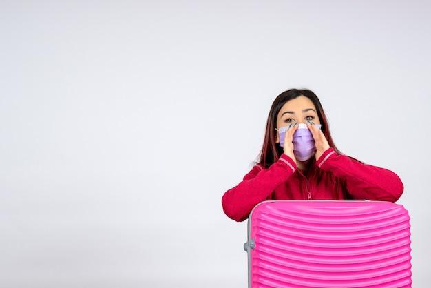 Vista frontale giovane femmina con borsa rosa in maschera sul muro bianco donna vacanza covid- viaggio pandemia virus colore
