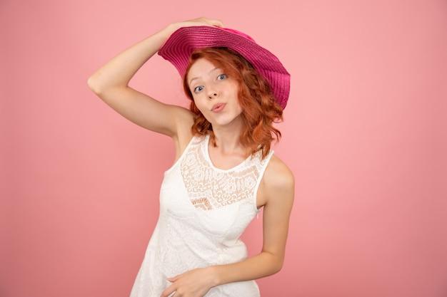 Vista frontale della giovane donna con cappello rosa sulla parete rosa chiaro