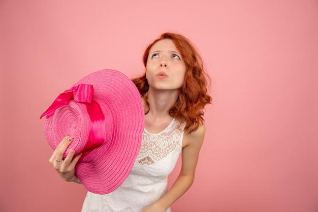 Vista frontale della giovane donna con cappello rosa sulla parete rosa