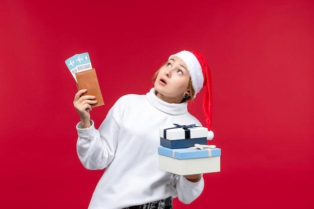 Вид спереди молодая женщина с билетами на самолет и подарками на красном фоне