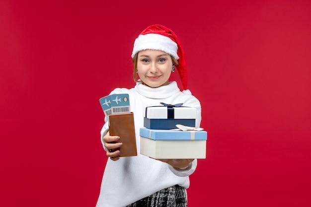 Вид спереди молодая женщина с билетами на самолет и подарками на красном столе