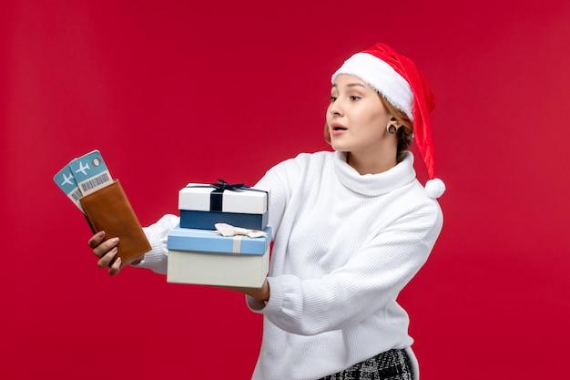 Вид спереди молодая женщина с билетами на самолет и подарками на красном полу новогоднее рождество красный