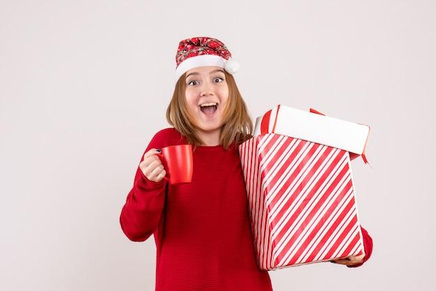 Вид спереди молодая женщина с подарком и чашкой чая