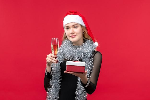 赤い壁の休日のクリスマスの色を祝うプレゼントと正面図若い女性