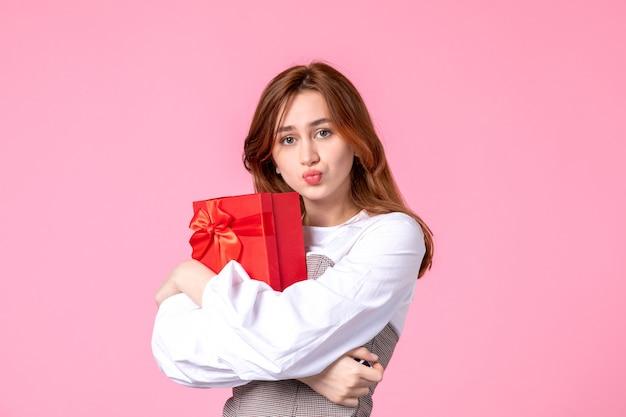 Вид спереди молодая женщина с подарком в красном пакете на розовом фоне, свидание, марш, горизонтальная любовь, женщина, чувственное равенство